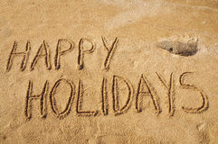 Happy Holidays. The words Happy Holidays written in the sand on the beach Stock Photography