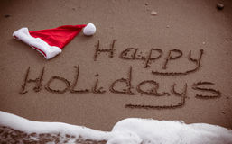 Happy holidays. The words Happy Holidays written in wet sand with a Santa Hat on a beach Royalty Free Stock Photography