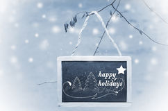 Happy holidays written on black chalk board hanging from a tree on blue, snowy background. Christmas tree ornament Royalty Free Stock Photos