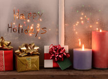 Happy Holidays. Written in the frost of a window with Christmas lights on the outside of the window. In front of the window are presents and lighted candles Stock Image