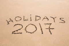 Happy Holidays 2017. Written in sand at the beach. Holiday, Christmas, New Year 2017 concept. Stock Photos