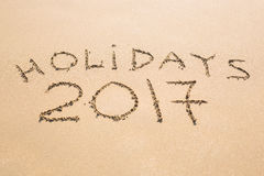 Happy Holidays 2017. Written in sand at the beach. Holiday, Christmas, New Year 2017 concept. Royalty Free Stock Photos