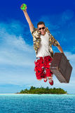 Happy holidays. A young, attractive male in a colorful outfit in a tropical island setting as a stereotype tourist stock images