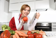 Happy home cook woman in apron at  kitchen using digital tablet as cookbook Royalty Free Stock Photography