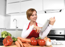 Happy home cook woman in apron at  kitchen using digital tablet as cookbook Stock Images