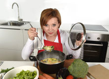 Happy home cook woman in red apron at domestic kitchen holding saucepan with soup tasting delicious vegetable stew Royalty Free Stock Photo