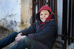 Happy homeless boy leaned against the wall Royalty Free Stock Photos