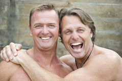 Happy homosexual couple. A happy laughing homosexual couple in their forties are cuddling and laughing as they have fun together outdoors stock photos