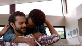 Happy homosexual couple men embracing. In living room stock footage