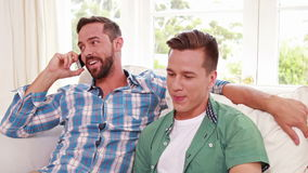 Happy homosexual couple men phoning stock footage