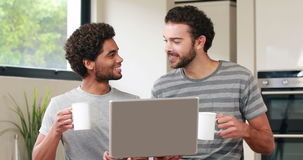Happy homosexual couple using computer stock footage