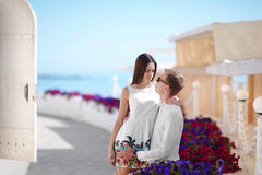 Happy honeymoon of a fall-in-love couple is walking outdoors. Beautiful girl hugging her boyfriend on a summer holiday. royalty free stock image