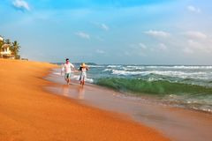 Couple running along the beach stock image