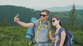 Happy Honeymoon. A young couple is photographed in the mountains, together in a hike. A young couple of tourists with backpacks take pictures of themselves with stock video