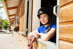 Happy horsewoman standing inside a box stall royalty free stock photography