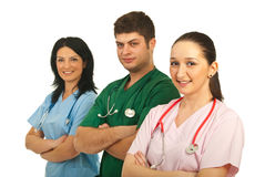 Happy hospital workers. Happy three hospital workers standing in a line with arms folded isolated on white background stock photos