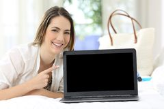 Hotel guest showing a blank laptop screen. Happy hotel guest showing a blank laptop screen on summer holidays stock image