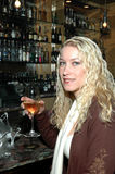 Happy Hour. Beautiful woman sitting at the bar drinking a glass of wine Royalty Free Stock Photography