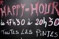 Happy hour. Foreground of a poster announcing the happy hour at a pub in paris royalty free stock photography