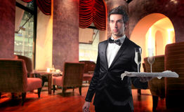 Happy hour. Handsome waiter serving some champagne in a lounge bar Stock Photo