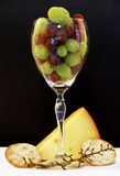 Happy Hour. Wine glass with grapes, cheese, crackers, grape stem Royalty Free Stock Photo