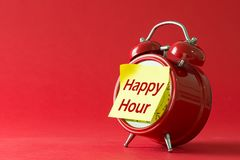 Happy hour with classic clock. Happy hour words written on sticky yellow note with red classic clock stock images