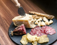 Happy Hour. A dark stone tray on a wooden kitchen table filled with parmesan cheese, salami and potato chips Stock Images
