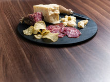 Happy Hour. A dark stone tray on a wooden kitchen table filled with parmesan cheese, salami and potato chips Stock Photography