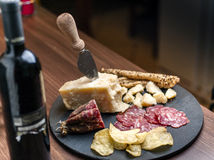Happy Hour. A dark stone tray on a wooden kitchen table filled with parmesan cheese, salami and potato chips Stock Photo