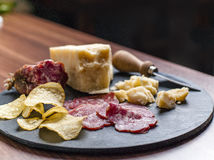 Happy Hour. A dark stone tray on a wooden kitchen table filled with parmesan cheese, salami and potato chips Stock Photos