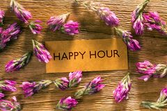 HAPPY HOUR. In looking memo on brown wood with beautiful red flowers around Stock Photos