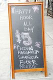 Happy Hour. A sign outside a drinking place advertises happy hour prices all day Royalty Free Stock Image