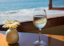 Happy Hour. A table & glass of wine at a quiet bar overlooking the ocean Stock Images