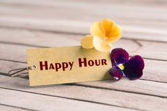 Happy hour tag. Tag banner happy hour and violet flower on wooden desk stock photography