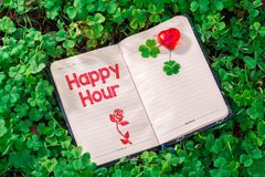 Happy hour text in notebook royalty free stock photo