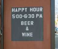Happy hour, wine and beer, sign outdoors. Happy hour, wine and beer, sign outside of a bar Stock Photos