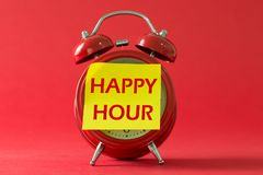 Happy hour with classic clock. Happy hour words written on sticky yellow note with red classic clock royalty free stock photography