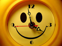 Happy hours. A yellow happy smiling clock Royalty Free Stock Photo
