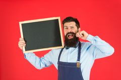 Happy hours bar. Man bearded bartender or cook in apron hold blank chalkboard. Price list concept. Hipster bartender. Show blackboard copy space. Hipster stock images