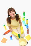 A happy house cleaning woman. On a floor with sponge and household chemistry bottles,bucket  isolated on a white background Stock Images