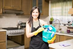 Young woman holding cleaning tools and products in bucket. Happy house maid wearing black apron over casuals holding bucket filled with bottles of detergents Royalty Free Stock Photography