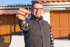 Happy house owner. Smiling young man holding keys and looking at camera while standing against new home background.  royalty free stock photos