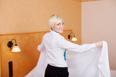Happy Housekeeper Making Bed In Hotel Room Stock Photos