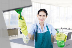 Happy housemaid cleans the mirror Stock Image