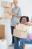 Happy housemates carrying cardboard moving boxes. And smiling at camera in new home Royalty Free Stock Image