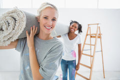 Happy housemates carrying rolled up rug in new home Royalty Free Stock Images