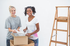 Happy housemates unpacking moving boxes Stock Image