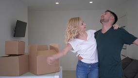 Happy housewarming, cheerful young couple new home owners fun dancing and take pleasure to new apartment with boxes stock footage