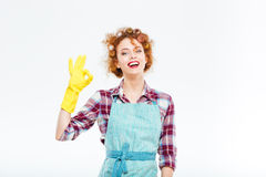 Happy housewife in apron and yellow gloves showing ok gesture Stock Images