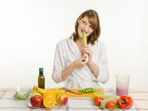 Happy housewife biting celery and looking up. Young beautiful girl in a bathrobe prepares vegetarian salad from vegetables and greens isolated on white Royalty Free Stock Photos